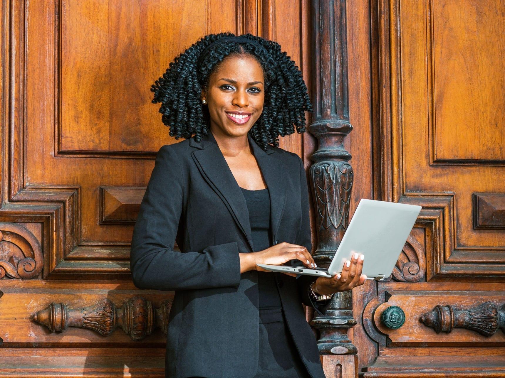 #PraCegoVer imagem ilustrativa de uma mulher advogada com um computador na mão. Ela sorri,